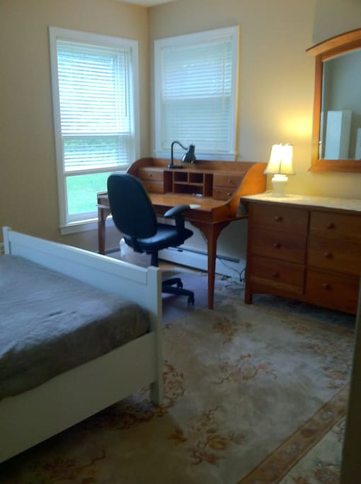 Desk, large dresser, and lots of light from three windows