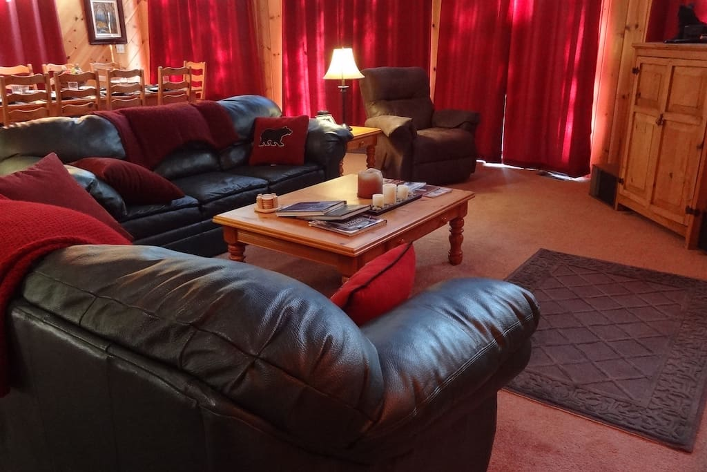 The great room has leather couches, a recliner, television, music, and a wood burning fireplace