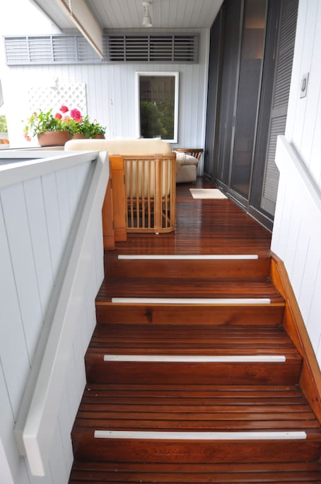 Small deck off the master bedroom with steps down to the pool.