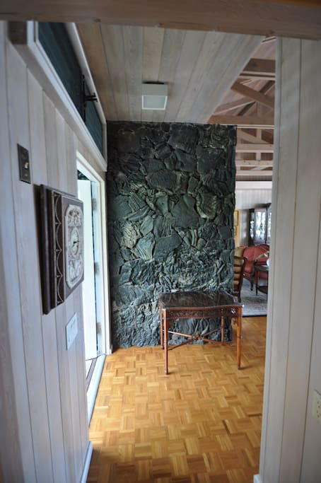 Main entrance showcases a large lava rock wall that extends outside, providing a sense of connecting the garden to the inside of the house. The outside portion of the wall is full of orchids.