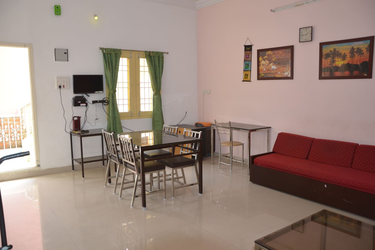 Living room consists of a TV, dining table, a sofa, working table, drinking water, 2 fans and a wardrobe.