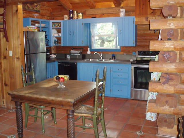 Kitchen with oven, range, full size refrigerator and stocked with dishes and cookware.