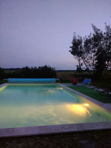 The pool is lit up at night, perfect for romantic twilight swims!