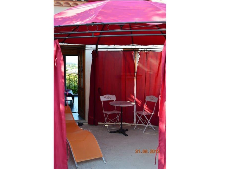 La terrasse ombragée par barnum, avec table et chaises de salon et transats. Derrière, le gîte traversant.