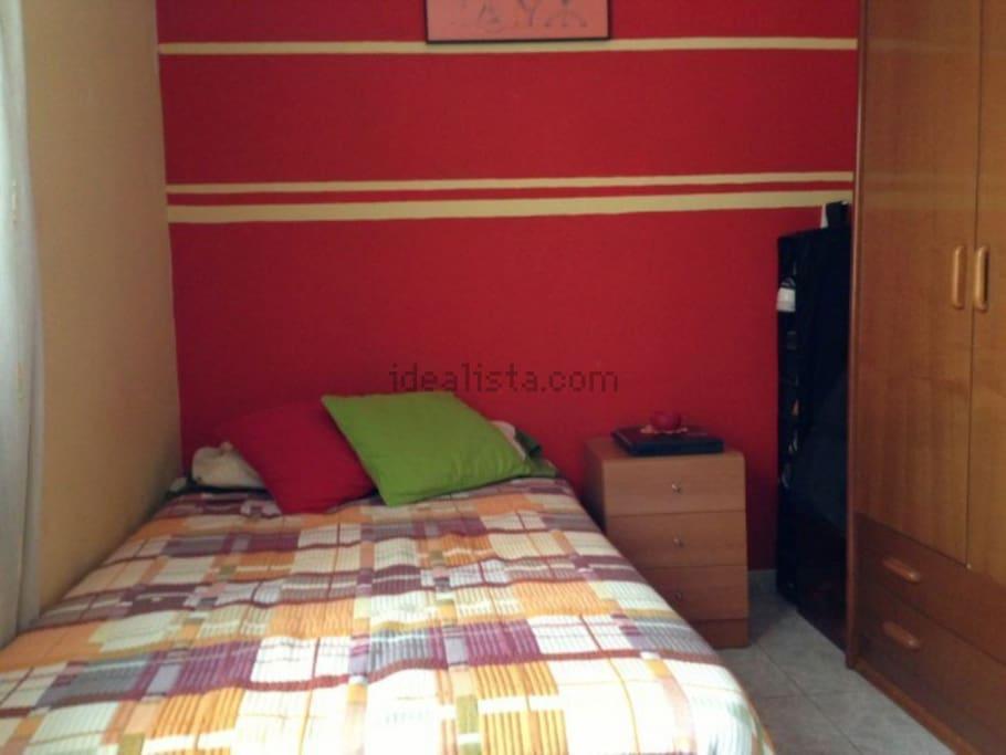 Amplia cama, mueble para ordenador con asiento ergonómico, amplio armario y mesa de noche y zapatero.