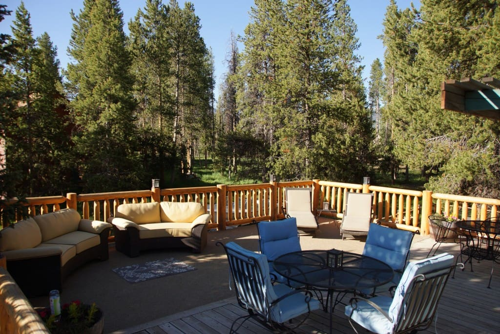 large outdoor living deck with sofas, chaise lounges and dining for 10.