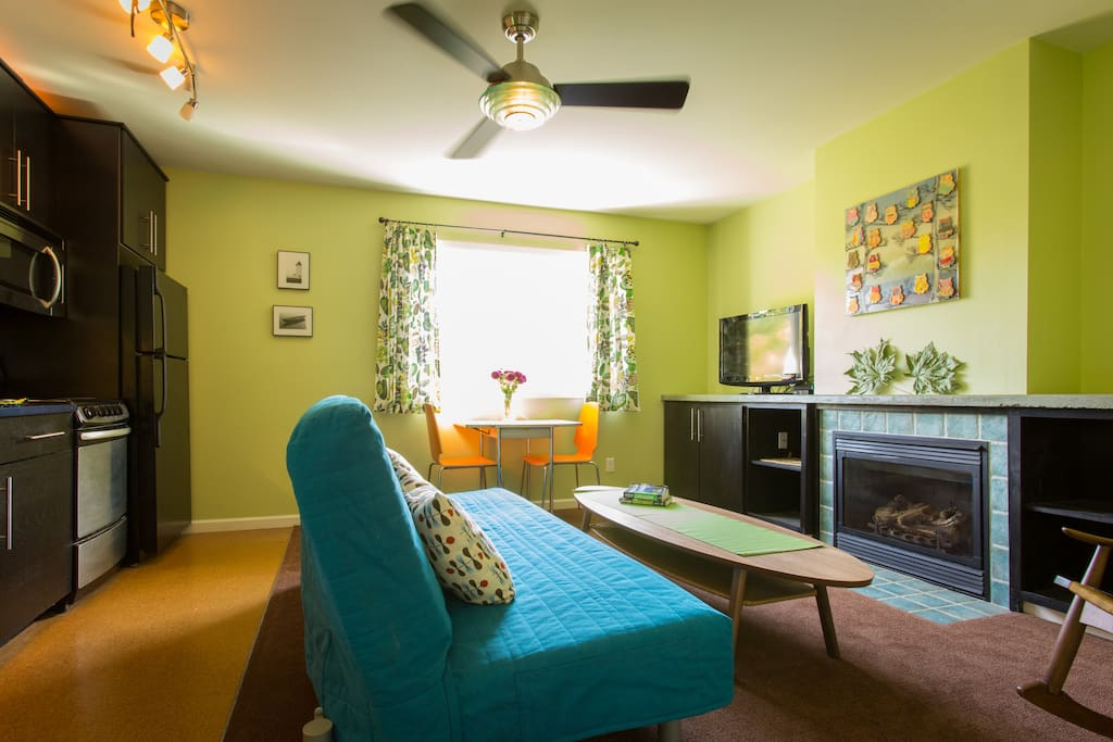 Bright living room and full kitchen with microwave, oven, full size refrigerator, and cooking essentials including pots and pans. The couch turns into a full size bed suitable for sleeping.