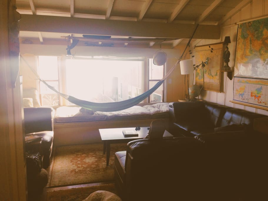 The homey living room with window seats, a large couch, hammock, and TV with cable