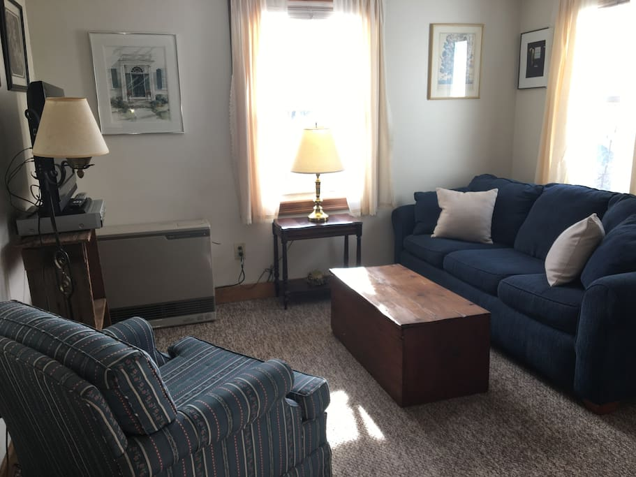 This view of the living room is from the bedroom. The living room has a sleep sofa, coffee table trunk stocked with games, a side table, TV with a VCR, a chair and a desk and chair. The apartment has cable and WiFi.