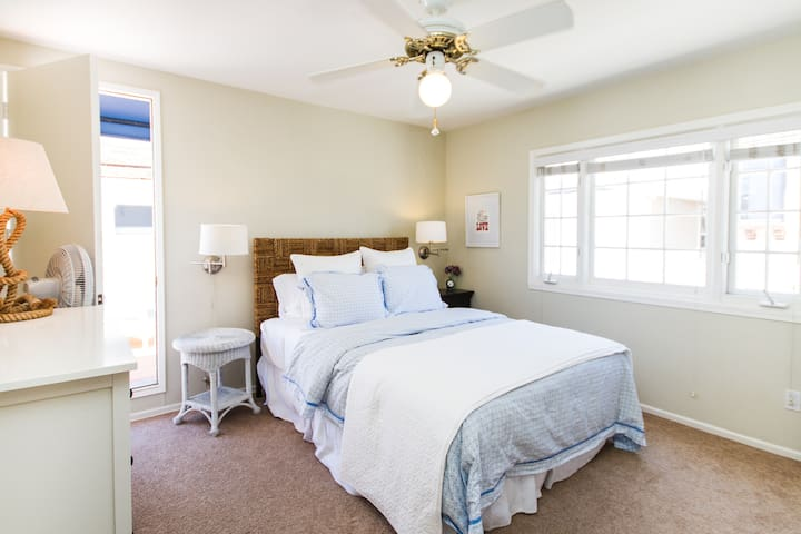 Queen bed in bright windowed bedroom. Door leads to sundeck. Lots of closet space, full length mirror and ceiling fan to keep cool.