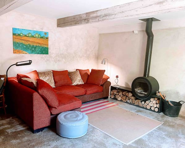 Salon: Sofa which is also fourth bed and wood burning stove.