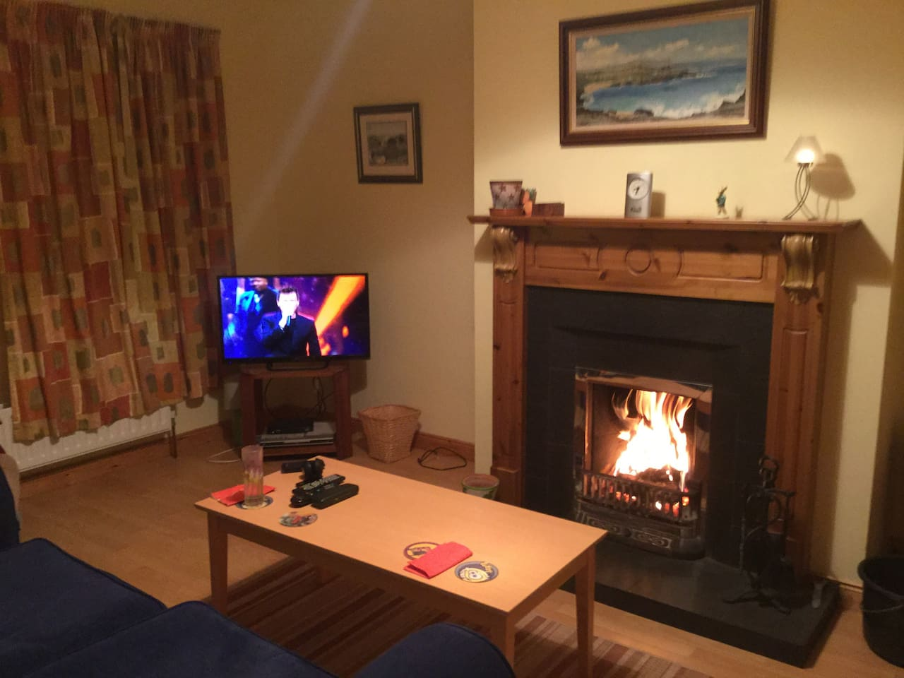 Living room with open fire, flat screen TV, satellite dish.