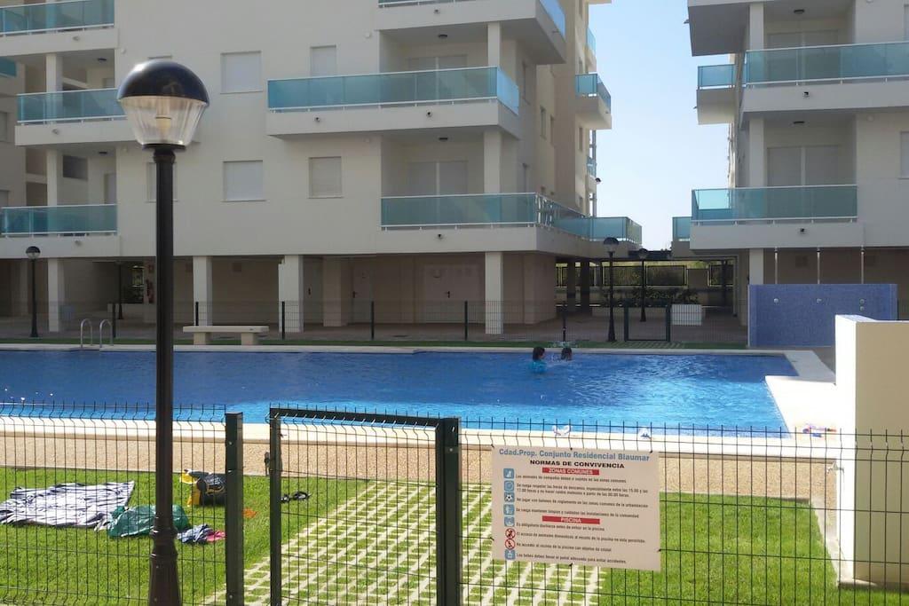 Preciosa piscina con instalaciones de aseos, pistas de padel y parque infantil