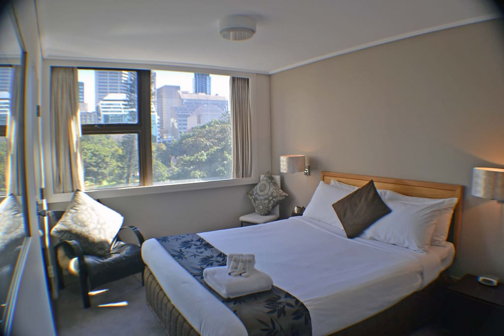 Sunny bed room with queen sized bed, park views and air con