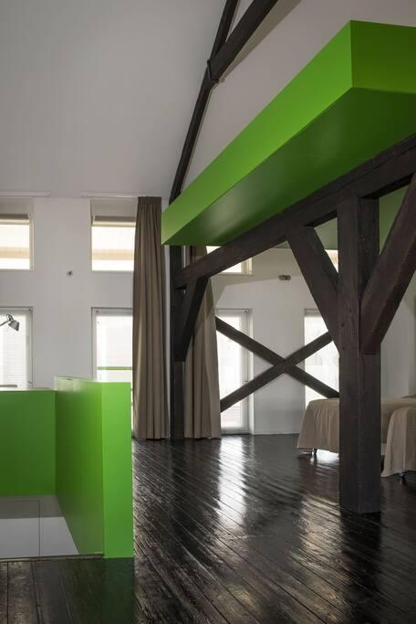Bovenverdieping met slaapplekken en werkplek.