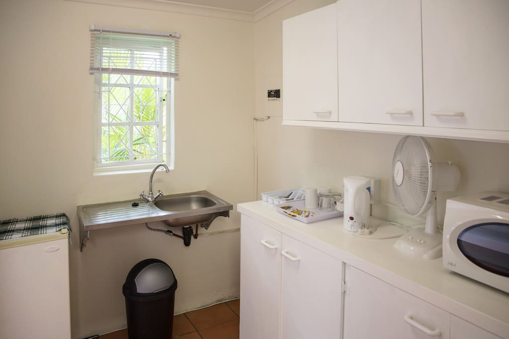 Kitchenette with fridge, microwave, crockery and cuttlery