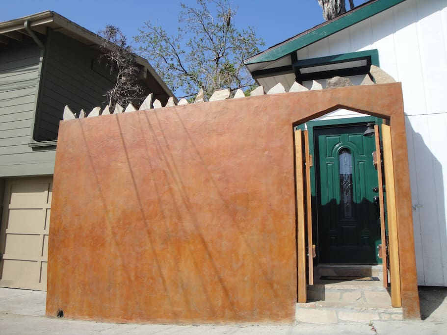 Terra cotta wall and gate open to reveal cottage front door