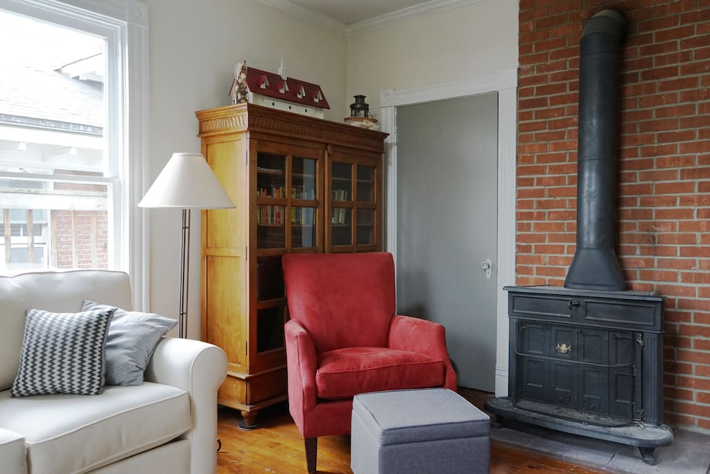 The big and comfy red chair next to the living room's beautiful black fireplace.