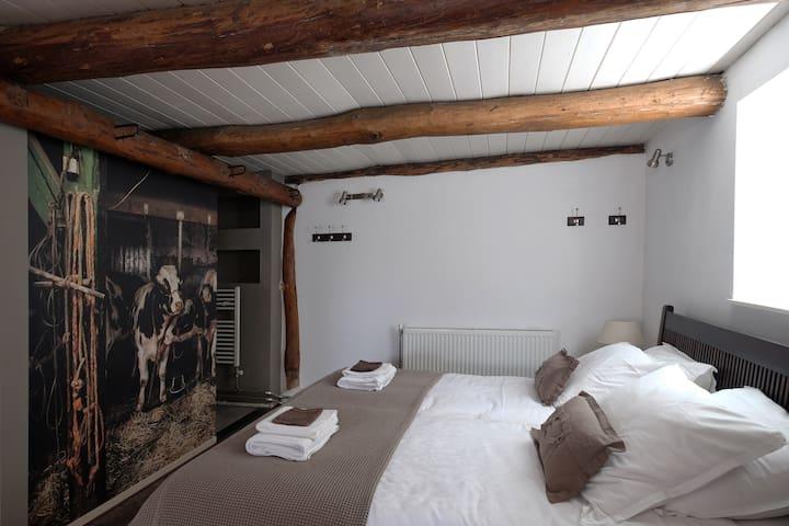Een breed bed met twee eenpersoons matrassen van 90 breed. Achter de 'koeienmuur' een ruime inloopdouche.