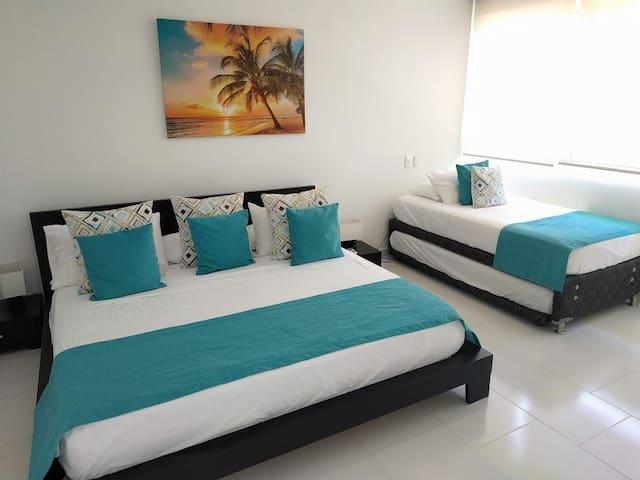 Habitación principal con cama king y dos camas sencillas, vestier  y baño