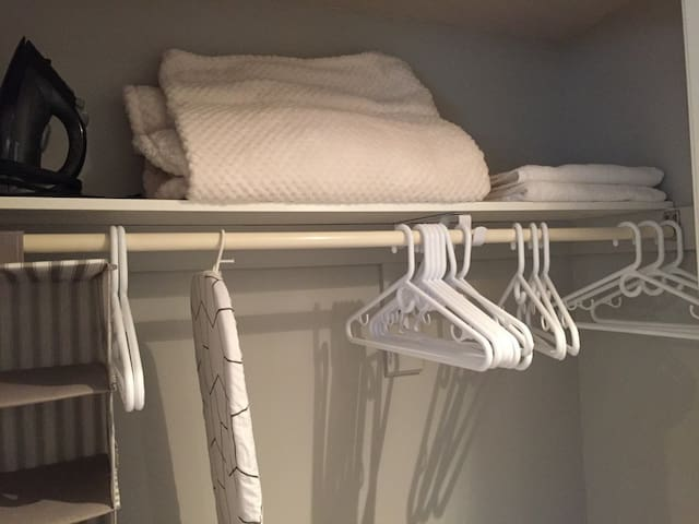 Iron, ironing board, extra blanket, extra towels, and assorted hangers in the bedroom closet