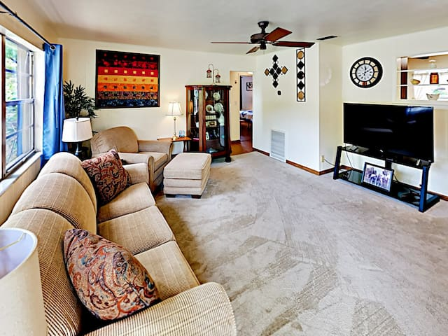 Cozy carpeting lines the sunny living room, furnished with a queen-size sleeper sofa and a matching armchair.
