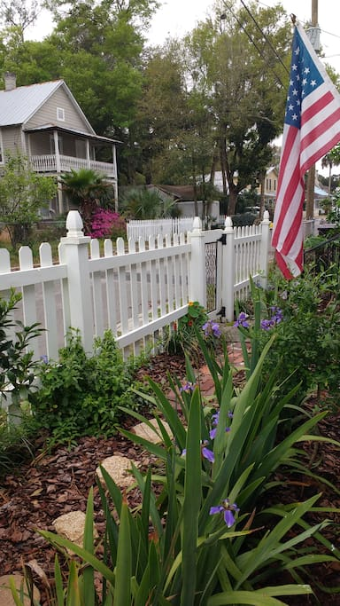the front yard is full of flowers and fruit trees.
