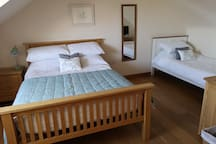 Triple bedroom with double bed and single bed.
