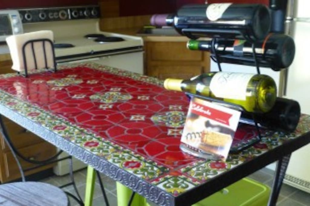 Tiled kitchen island with bar stools and stocked wine rack