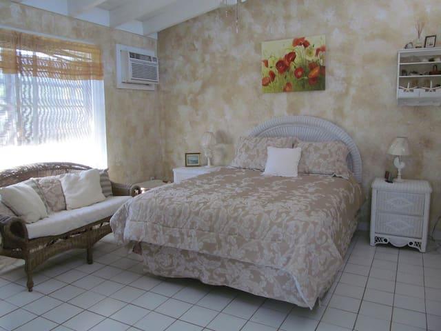 Romantic bedroom has queen size bed, loveseat...