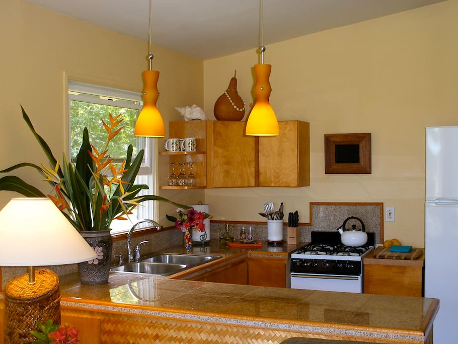 The kitchen features pendant lighting over granite tiled countertops, a full sized refrigerator, double sink, four-burner cook-top and oven. It is a culinary paradise!