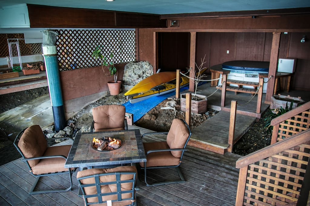 Best indoor/outdoor space with fire pit table on the water, outdoor shower, and two kayaks.