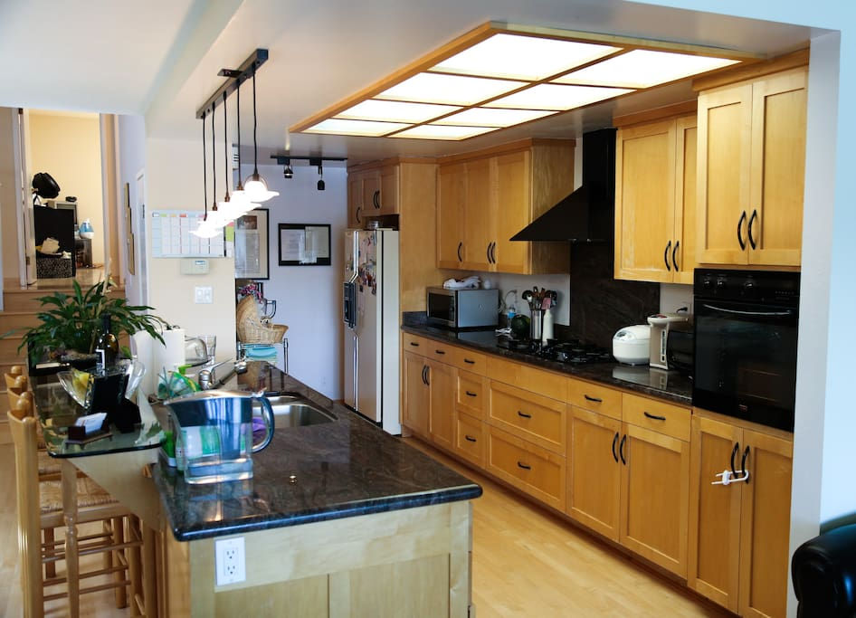 Gourmet kitchen with granite countertop, wine refrigerator, and top-of-line cookware.
