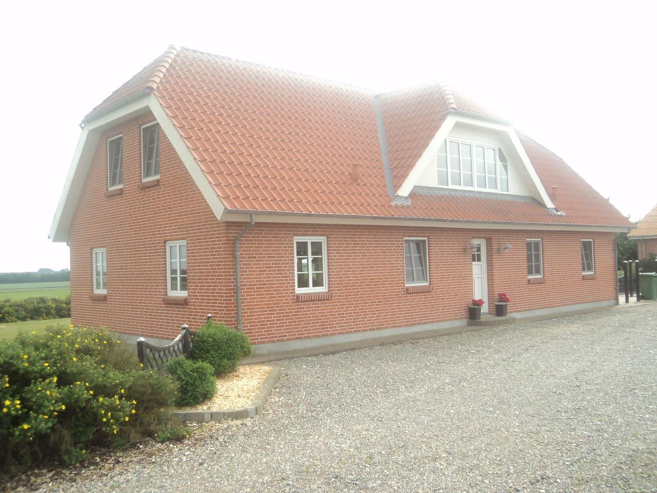 Huset udefra - stor gårdsplads foran og have bagved.