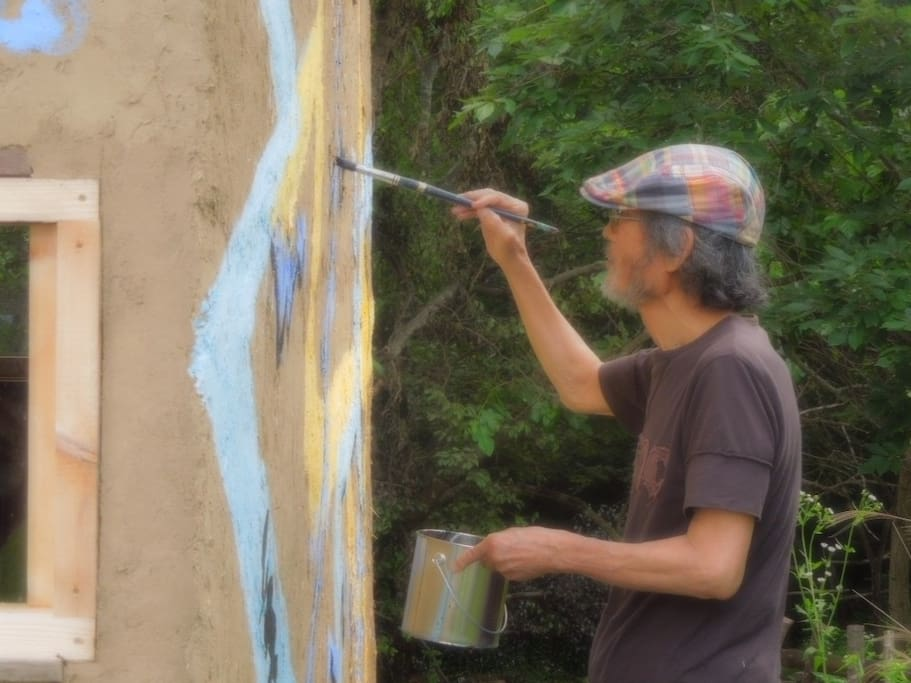 Taslima Seizou , a famous painter is drawing his work on the wall of Seizou House.