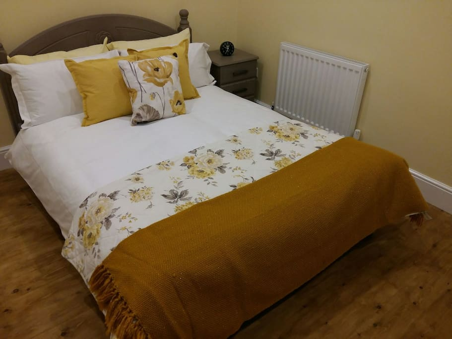 Comfortable bed in a bright, newly refurbished room.