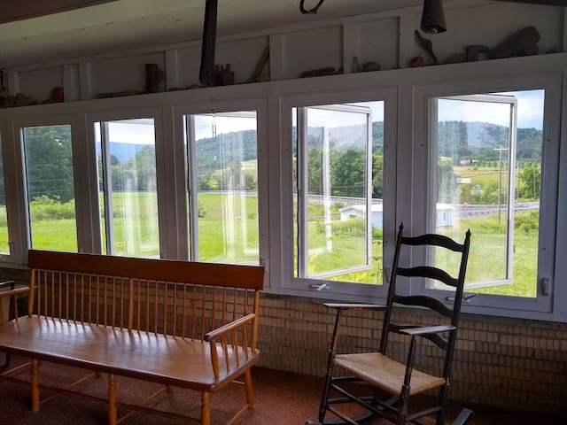 Beautiful enclosed porch with windows on 3 sides.