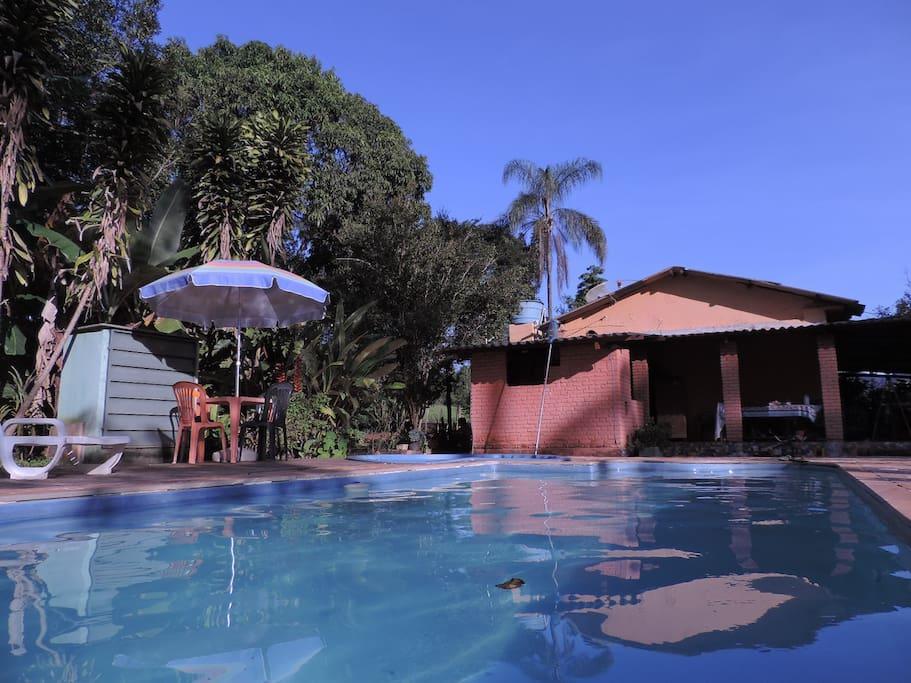 Área de lazer da piscina e casa principal ao fundo