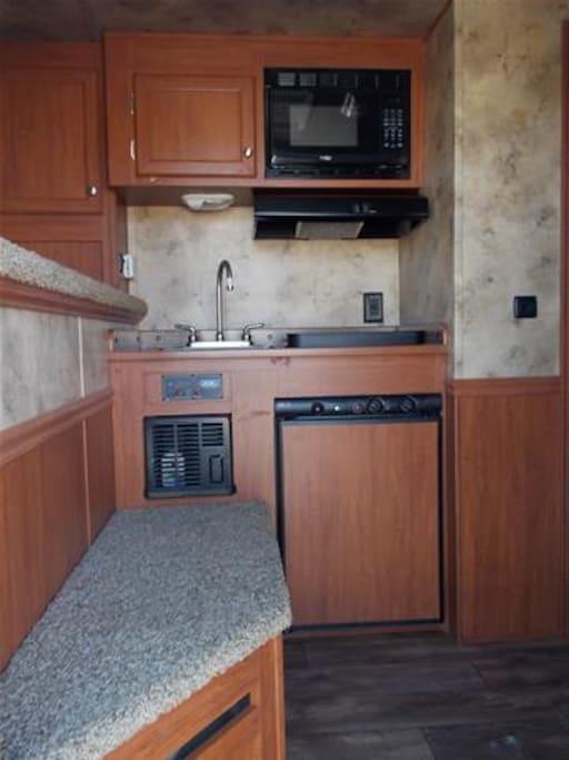 Kitchenette with microwave, fridge, sink