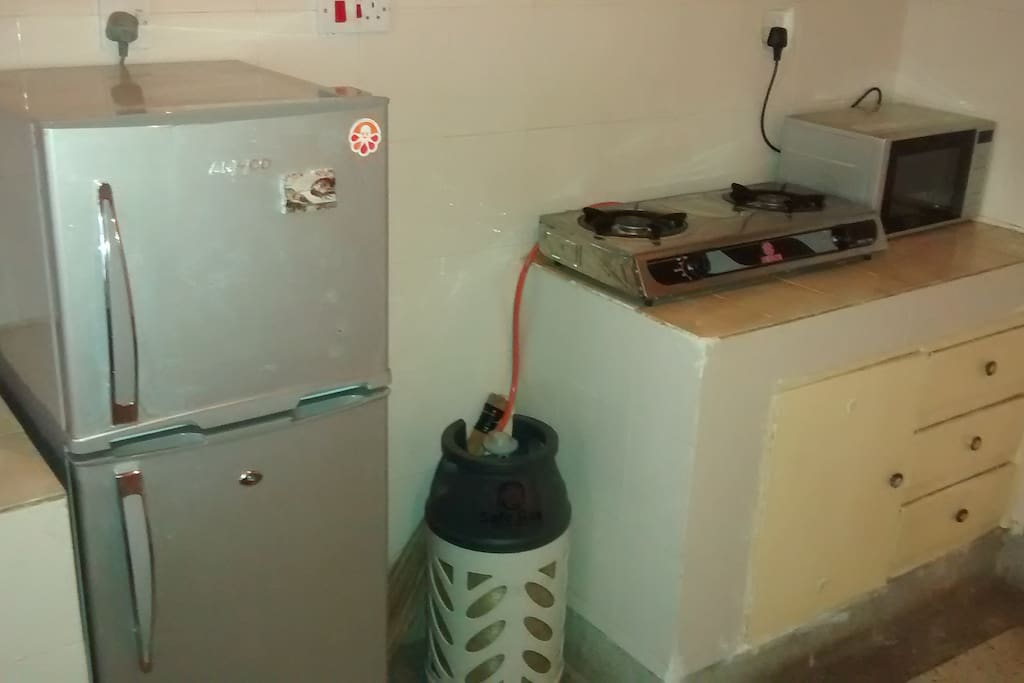 Kitchen with fridge, microwave, burner stove, kettle and dishes