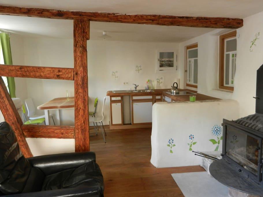 Blick in die offene Küche mit Essecke. Rechts der Kamin