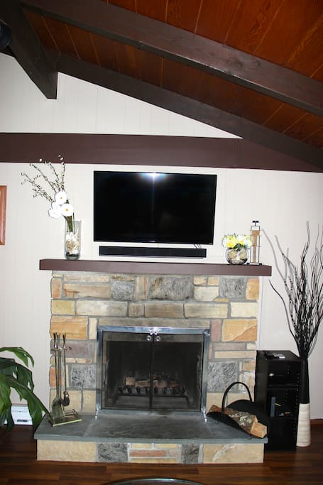 Wood burning fireplace with 48' smart HDTV, soundbar and DVD