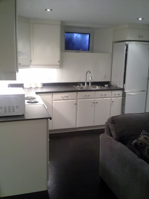 Kitchen contains refridgerator, electric stove, microwave, pots, pans, dishes, utinsels.