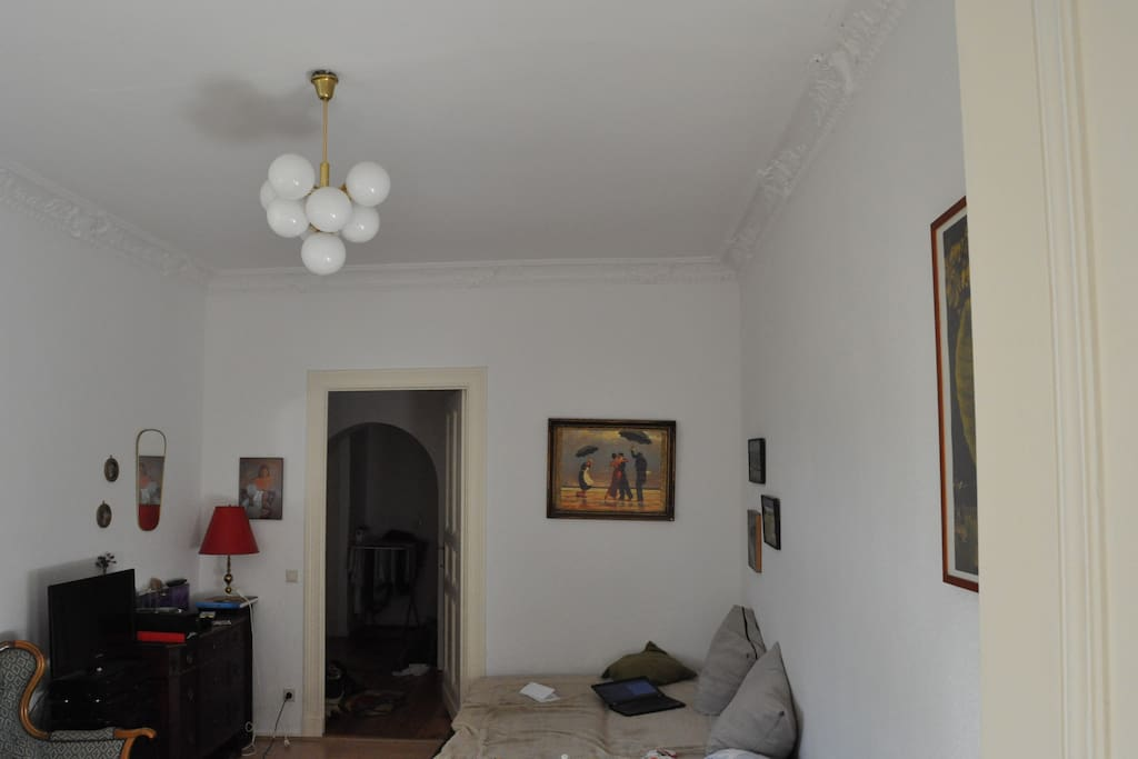Im geräumigen Wohnzimmer steht ein kleiner Fernseher, ein Esstisch und eine Couch