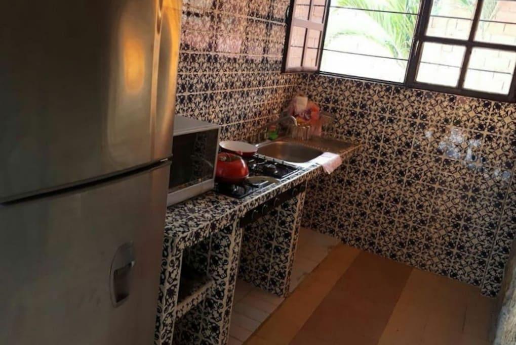 Cocina cuenta con refrigerador, horno, estufa, lavabo y utensilios.