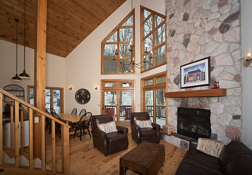 Living room with vaulted ceiling, wood-burning fireplace, gorgeous mountain views and plenty of space for entertaining!