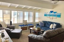 The living room has a queen size pull-out sofa sleeper, chair/ottoman and a full size love-seat with additional bedsheets and pillows.