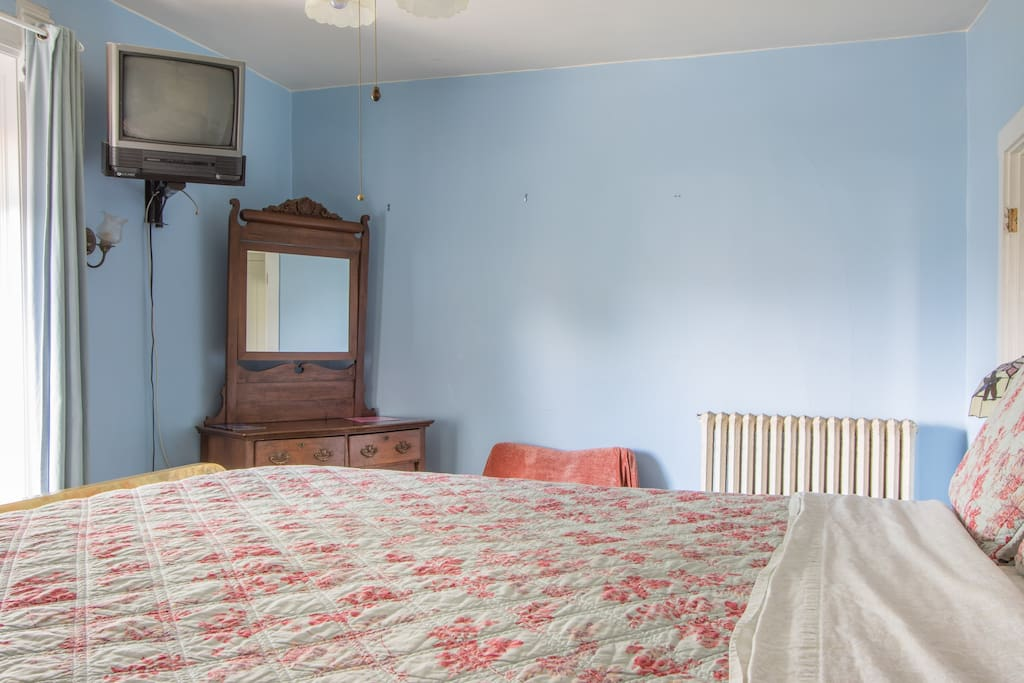Room includes a small chair, dresser and twin mattress stored under the bed to accommodate more guests.
