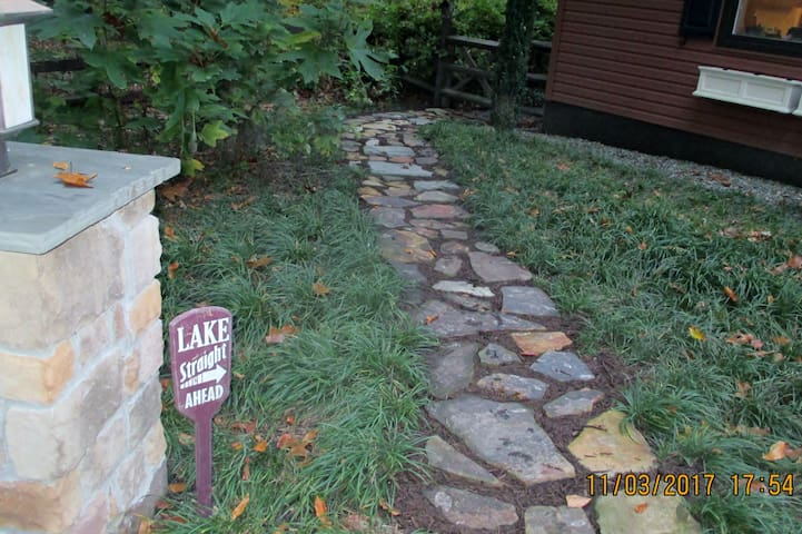 Path leading from parking area around our home and down to the lake.  (you can also go around the other side of the house from your unit).