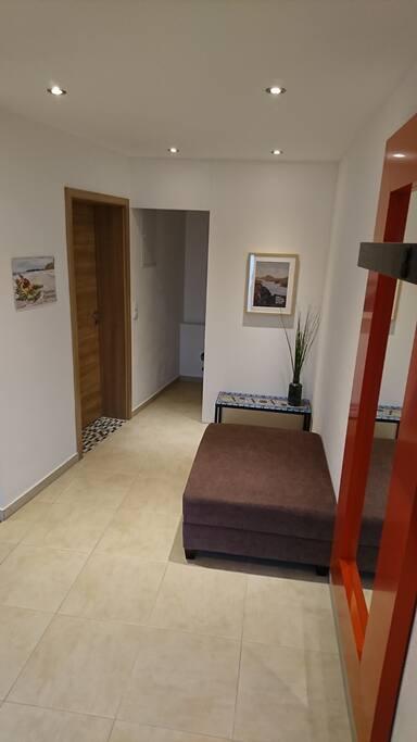 Eingangsbereich mit Garderobe und großem Spiegel zum Ankleiden. Entrance area with wardrobe and big mirror to get dressed.